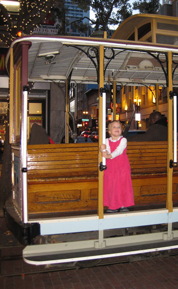 Modest clothing on an adorable child riding a San Francisco cable car!
